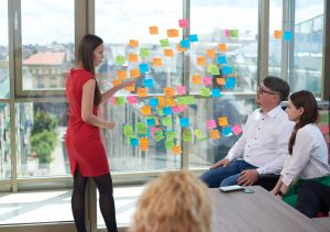 Agile meeting, woman in red points at colorful post-its